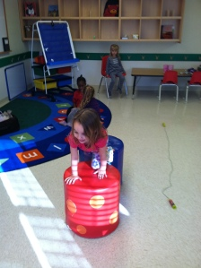 A student at the Primrose School climbs through an Obstacle Course.